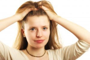 Woman scratching head psoriasis