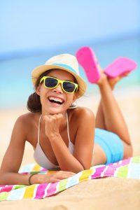 girl on beach hat glasses on beach